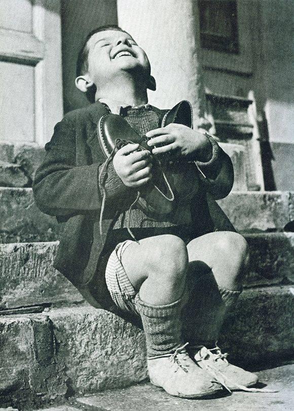 Un niño austriaco recibe unos zapatos nuevos durante la Segunda Guerra Mundial.