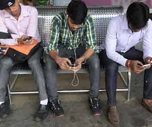 Jóvenes indios hacen uso de sus smartphones en una estación de Bombay. Foto: AFP.