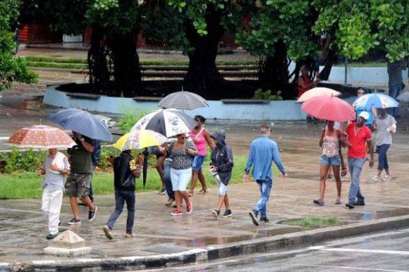 Personas protegiéndose de la lluvia al transitar por el Vedado, en La Habana, Cuba, el 30 de agosto de 2016.   Foto: Omara García Mederos / ACN