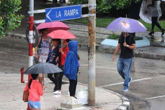 Personas protegiéndose de la lluvia al transitar por el Vedado, en La Habana, Cuba. Foto: Omara García Mederos / ACN