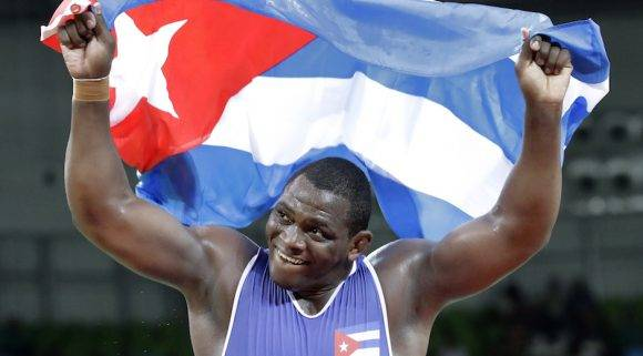 Cuba's Mijain Lopez Nunez celebrates after beating Turkey's Riza Kayaalp to win the gold in the men's wrestling Greco-Roman 130-kg competition at the 2016 Summer Olympics in Rio de Janeiro, Brazil, Monday, Aug. 15, 2016. (AP Photo/Charlie Riedel)