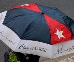 Persona protegiéndose de la lluvia al transitar por el Vedado, en La Habana, Cuba, el 30 de agosto de 2016.   Foto: Omara García Mederos / ACN