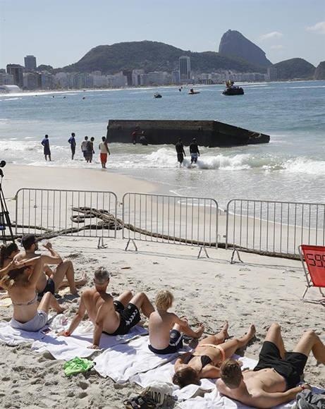 La plataforma desde donde deberían salir los nadadores de la prueba a mar abierto se hundió y llegó hasta la playa. Foto: EFE.