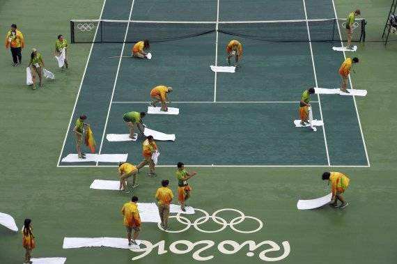 2016 Rio Olympics - Tennis - Semifinal - Men's Doubles Semifinals - Olympic Tennis Centre - Rio de Janeiro, Brazil - 10/08/2016. The centre court is cleaned by personnel after matches were delayed due to rain. REUTERS/Toby Melville FOR EDITORIAL USE ONLY. NOT FOR SALE FOR MARKETING OR ADVERTISING CAMPAIGNS.