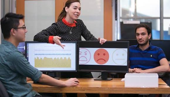Dina Katabi (centro) explica que la expresión facial de Fadel Adib (derecha) es neutra, pero que el análisis que el sistema EQ-Radio ha hecho de su ritmo cardíaco y su respiración muestra que está triste. Foto: Jason Dorfman/MIT CSAIL