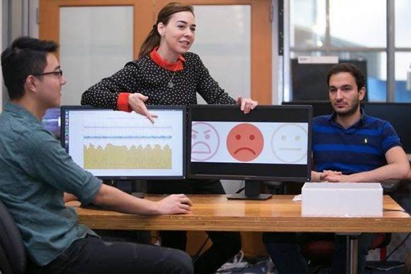 Dina Katabi (centro) explica que la expresión facial de Fadel Adib (derecha) es neutra, pero que el análisis que el sistema EQ-Radio ha hecho de su ritmo cardíaco y su respiración muestra que está triste. (Foto: Jason Dorfman/MIT CSAIL)