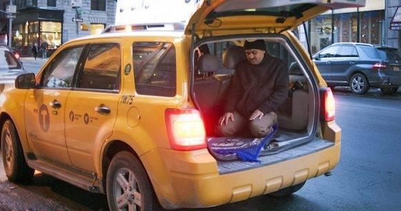 Un taxista musulmán reza en el maletero de su vehÌculo en la ciudad de Nueva York. Foto: EFE/Sebastian Gabriel.