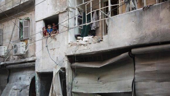 Niños sirios se asoman por la ventana de un edificio derrumbado por los bombardeos en Alepo. Foto: AFP.