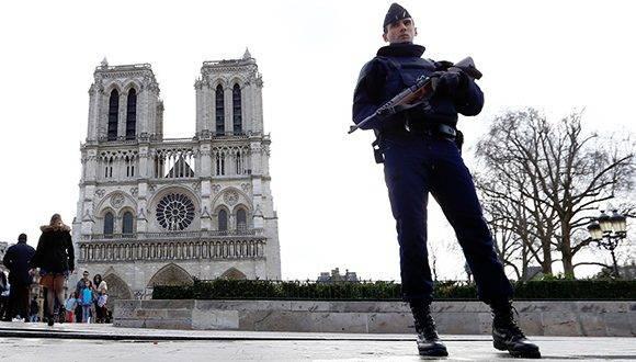 Un policía francés monta guardia mientras las personas llegan a Notre Dame. Foto AFP