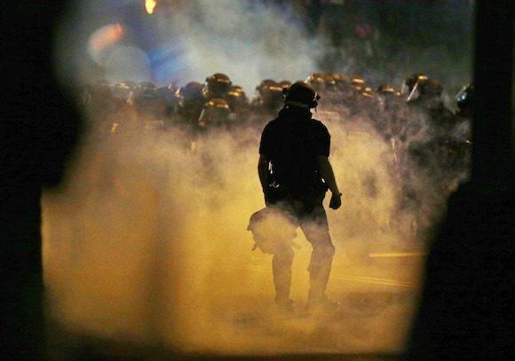 gases lacrimógenos contra incendios de la policía como los manifestantes convergen en el centro después de disparos de la policía del martes de Keith Lamont Scott, en Charlotte, Carolina del Norte, miércoles, 21 de septiembre de 2016. Los manifestantes se han apresurado la policía antidisturbios en un hotel del centro de Charlotte y agentes han disparado gases lacrimógenos para dispersar a la multitud. Al menos una persona resultó herida en el enfrentamiento, aunque no estaba claro cómo. Los bomberos acudieron a tirar del hombre a una ambulancia. (Foto AP / Gerry Broome)