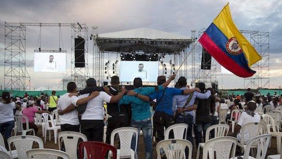 los hombres se abrazan y sostienen una bandera de Colombia durante un evento organizado por rebeldes de las Fuerzas Armadas Revolucionarias de Colombia (FARC) en el Yari Llanuras del sur de Colombia, mientras ven imágenes en directo en las pantallas de gobierno y líderes de las FARC firman un acuerdo de paz en Cartagena poner fin a más de cinco décadas de conflicto, lunes, 26 de septiembre de 2016. (Foto AP / Ricardo Mazalan)