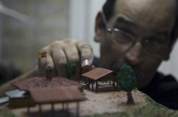 Paul Chaviano coloca una de sus maquetas a la altura de sus ojos y recuerda su infancia. Foto: Ladyrene Pérez/ Cubadebate.