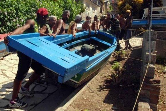 Vecinos de Cayo Granma, ponen a buen recaudo sus embarcaciones por la amenaza del Huracán Mathew, en la bahía de Santiago de Cuba, el 2 de octubre de 2016. Foto: Miguel Rubiera Jústiz / ACN