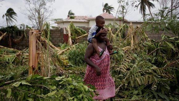 Una mujer lleva un niño caminando entre los árboles talados por el huracán Mateo en Les Cayes, Haití. Foto: Reuters.