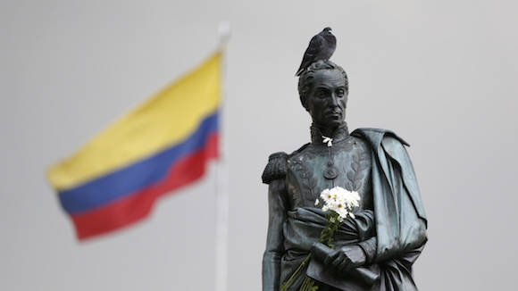 Flowers decorate the statue of independence hero Simon Bolivar at the main square in downtown Bogota, Colombia, Friday, Oct. 7, 2016.  President Juan Manuel Santos won the Nobel Peace Prize Friday, just days after voters narrowly rejected a peace deal he signed with rebels of the Revolutionary Armed Forces of Colombia, FARC.  (AP Photo/Fernando Vergara)