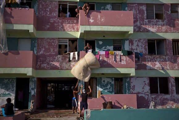 Residentes de Baracoa descuelgan un colchón desde un tercer piso de un edificio que sufrió el embate del huracán Matthew en Baracoa. Foto: Ramon Espinosa/ AP