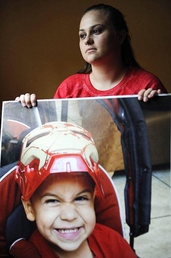 Crystal Mees-Hernández posa para una foto sosteniendo una foto enorme de su hijo Bryson, fallecido a los cuatro años al pegarse un tiro con un arma que encontró en la casa de su abuela. La mujer responsabiliza a su madre por la muerte del pequeño, por haber dejado el arma al alcance del niño. La madre tenía el arma escondida debajo de su cama. Foto del 13 de agosto del 2016 en Houston. (AP Photo/Eric Christian Smith)