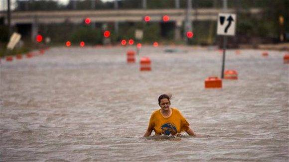 Mujer camina entre las aguas en Georgia EE UU tras paso de huracán Matthew. Foto: AP
