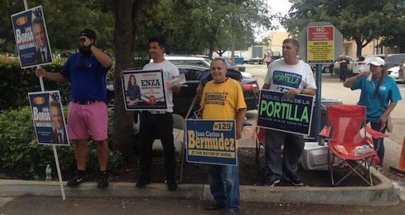 Personal pagado por las campañas de varios candidatos, cerca de un colegio electoral donde ya se vota en Miami.