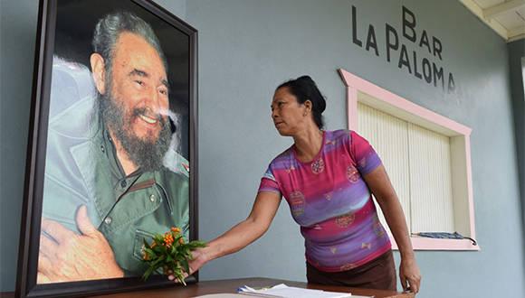 A pocas horas del fallecimiento del lider de la Revolución cubana, trabajadora del Conjunto Histórico de Birán rinde homenaje a Fidel Castro al depositar flores bajo su retrato, en Birán, Holguín. Noviembre 26 de 2016. Foto/ Heidi Calderón Sánchez.
