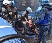 Policías arrastran por el piso a uno de los manifestantes. Foto: EFE.