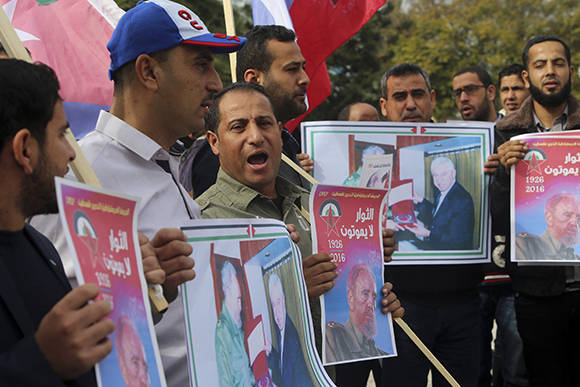 Palestinians chant slogans as they hold pictures of the late Fidel Castro, leader of the Cuban revolution, who died at the age of 90 on November 25, 2016, during a protest on the international solidarity day with Palestinian people at the Unknown soldier square in Gaza City, Tuesday, Nov. 29, 2016. (AP Photo/Adel Hana)