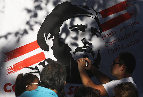 A man takes a pictures with his cellphone during a gathering to mourn the death of Cuba's leader Fidel Castro, outside the Cuban embassy in Santiago, Chile, Sunday, Nov. 27, 2016. Castro, who led a rebel army to improbable victory, embraced Soviet-style communism and defied the power of 10 U.S. presidents during his half century rule of Cuba, died Friday at age 90. (AP Photo/Esteban Felix)