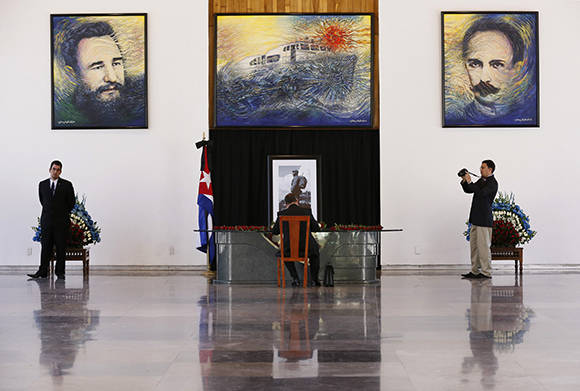 A person signs a book of condolences for the late Cuban President Fidel Castro at the Cuban embassy in Mexico City, Monday, Nov. 28, 2016. Castro, who led a rebel army to improbable victory, embraced Soviet-style communism and defied the power of 10 U.S. presidents during his half century rule of Cuba, died at age 90 in Cuba late Friday. (AP Photo/Marco Ugarte)