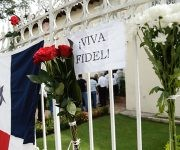 Flowers are attached to the gate of the Cuban Embassy to honor the late Cuban leader Fidel Castro, where people lined up to pay tribute and sign a condolences book, in Panama City, Panama, Monday, Nov. 28, 2016. Castro, who led a rebel army to improbable victory, embraced Soviet-style communism and defied the power of 10 U.S. presidents during his half century rule of Cuba, died Friday at age 90. (AP Photo/Arnulfo Franco)