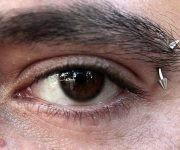"""Un """"piercing"""" adorna la ceja de un joven, en el barrio de Vedado, en capital de Cuba. Crédito: Jorge Luis Baños/ IPS."""