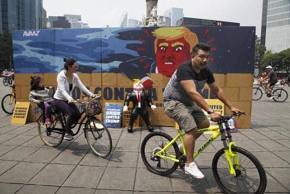 Una pareja pasa en bicicleta junto al mural contra Donald Trump frente al Ángel de la Independencia. Foto: AP.