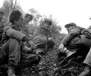 Camilo Cienfuegos, Fidel Castro y Che Guevara, de derecha a izquierda, escuchan las informaciones que les da Maracaibo, un explorador que acababa de regresar de las líneas enemigas durante el combate de Pino del Agua, en septiembre de 1957. Foto: Enrique Meneses.