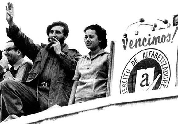 """Fidel saluda a los alfabetizadores en la concentración en la Plaza de la Revolución """"José Martí"""", para proclamar a Cuba Territorio Libre de Analfabetismo, lo acompaña una joven alfabetizadora, el 22 de diciembre de 1961. Fuente: Periódico Escambray / Sitio Fidel Soldado de las Ideas."""