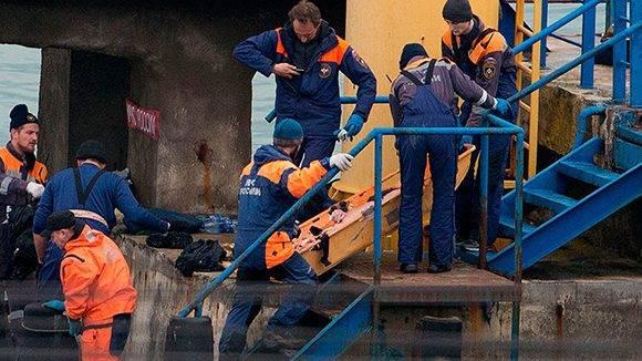 Personal de rescate trasladan el cadáver de un pasajero del avión Tu-154. Foto: AFP.