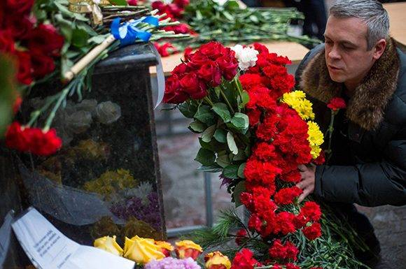 Un hombre deposita flores en al sede del coro del Ejército Rojo en Moscú. Foto: AFP.