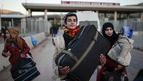 Una familia después de haber cruzado la frontera turca con Siria, tras haber salido de Alepo. Foto: AP.