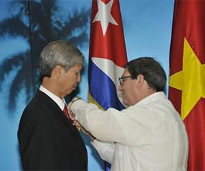 El Ministro de Relaciones Exteriores, Bruno Rodríguez Parrilla, entrega la Medalla de Amistad al embajador vietnamita , Duong Minh. Foto: VNA.