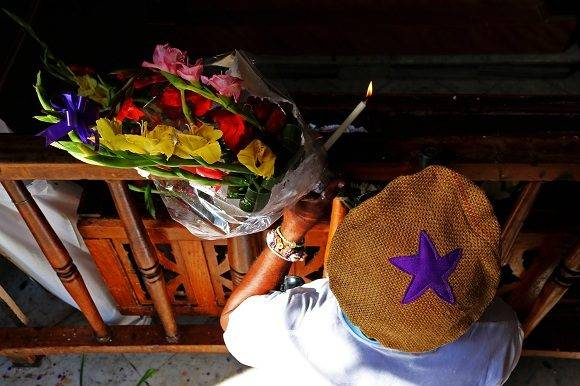 Las flores y velas son las ofrendas más comunes con las que los devotos agasajan a San Lázaro en los altares. Encender una llama simboliza la intención de iluminar el camino de aquel por quien se prenda. Foto: Darío Gabriel Sánchez García/CUBADEBATE.