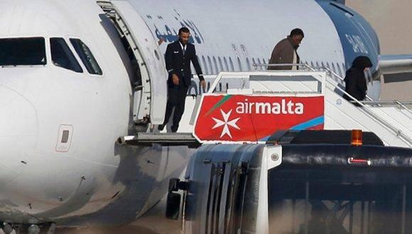 Pasajeros del vuelo secuestrado descienden del avión tras ser liberados. Foto: Reuters.