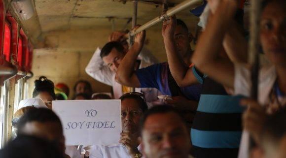 """Una mujer muestra una señal hizo dice en español """"Estoy Fidel"""" mientras se monta con otros en un autobús que se dirige a Bamayo para la procesión funeraria llevar las cenizas de Fidel Castro en Bartolomé Masó, una ciudad en las estribaciones de la Sierra Maestra, Cuba, Viernes , diciembre 2, 2016. cenizas de Castro están en un viaje de cuatro días a través de Cuba a través de pequeños pueblos y ciudades, donde su ejército rebelde se abrió paso al poder hace casi 60 años, a su lugar de descanso final en la ciudad oriental de Santiago. (Foto AP / Natacha Pisarenko)"""