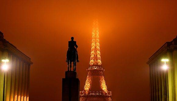 A picture taken on January 24, 2017 in Paris shows the statue of the Marshal Foch at the Trocadero, with a view of the top of the Eiffel Tower hidden by the fog in the background. / AFP PHOTO / FRANCK FIFE