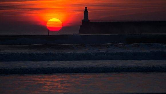A picture taken on January 24, 2017 shows a lighthouse on a pier at sunset in Les Sables d'Olonne, western France. / AFP PHOTO / JEAN-SEBASTIEN EVRARD