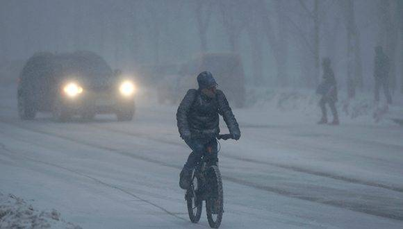 A man rides a bicycle on a snowy road in Kiev, Ukraine, Wednesday, Jan. 25, 2017. The temperature was - 3 C (F 27) in Kiev on Wednesday. (AP Photo/Sergei Chuzavkov)