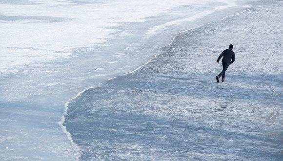 A man skates over the frozen Olympiasee lake at the Olympic Parc in Munich, southern Germany, where temperatures were around minus seven degrees Celsius on January 23, 2017. / AFP PHOTO / dpa / Sven Hoppe / Germany OUT