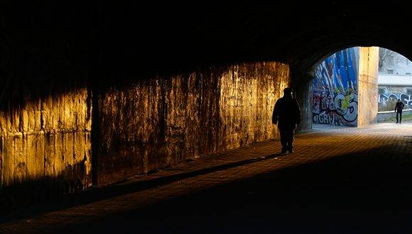 A man walks in a tunnel under a bridge in Milan, Italy, Wednesday, Jan. 25, 2017. (AP Photo/Luca Bruno)