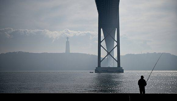 A fisherman stands under the 25th of April Bridge from the Tagus riverside in Lisbon on January 25, 2017. / AFP PHOTO / PATRICIA DE MELO MOREIRA