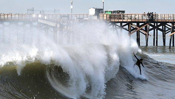 Surfers and body boarders ride waves on the south side of the Seal Beach Pier after a series of powerful winter storms in Seal Beach, Calif., Tuesday, Jan. 24, 2017. (Jeff Gritchen/The Orange County Register via AP)
