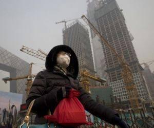 Una mujer que viste una mascarilla facial pasa por delante de una obra bajo la persistente smog que cubre Beijing, el 6 de enero de 2017. Foto: AP.