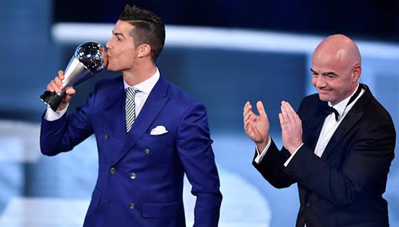 Cristiano Ronaldo besa el trofeo a mejor jugador de 2016 ante la mirada de Gianni Infantino, presidente de la FIFA Foto. Fabrice Coffrini/ AFP.