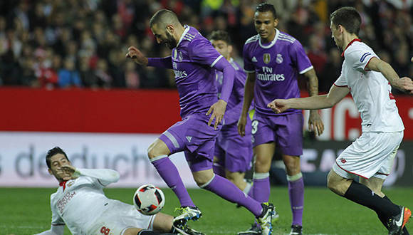 El jugador del Real Madrid, Benzema, regatea a varios jugadores sevillistas en la jugada que supuso el tercer gol y empate de su equipo ante el Sevilla FC. PACO PUENTES